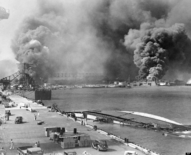 In this image provided by the U.S. Navy, a pall of smoke filled the sky over Pearl Harbor, Hawaii on Dec. 7, 1941, after the Japanese attacked. In the foreground is the capsized minelayer, the USS Oglala, and to the left appears the moored USS Helena, 10,000-ton cruiser, struck by a bomb. Beyond the superstructure of the USS Pennsylvania, and at the right is the USS Maryland, burning. At right center the destroyer Shaw is ablaze in drydock. (AP Photo/U.S. Navy)